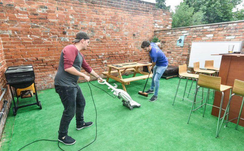 PIC BY MICHAEL SCOTT/CATERS NEWS - Cameron Smith (20) and Matthew Meekins (21) clean the astroturf.