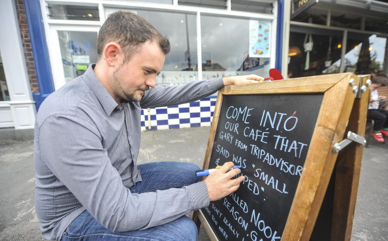 PIC BY DAN ROWLANDS/MERCURY PRESS (PICTURED: NOOK NEIGHBOURHOOD CAFE MANAGER ARLO CALDERBANK, 27, WRITING A MESSAGE ON ONE OF THE BOARDS OUTSIDE THE CAFE)  A caf owner is hitting back at negative TripAdvisor reviews  by writing them up on their A-board in bid to lure in customers with the worst porridge one woman had in her life. Arlo Calderbank, 27, manager at the Nook Neighbourhood Caf in Stockport, Greater Manchester, was stunned by the vitriolic comments left on the popular review website. Rather than let the reviews get him down, Arlo instead began writing them on the black board in a series of tongue-in-cheek messages, which have gone viral  online  clocking up more than 12,000 likes and 2,000 shares.SEE MERCURY COPY