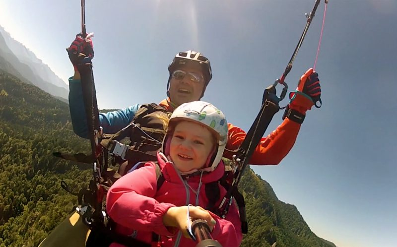 PIC BY MIK BROSCHART/ CATERS NEWS - (PICTURED: Emilia and her dad Mik paraglide over beautiful Brauneck mountain.) - This little girl loves to do a little PARA-GLOATING as she soars above the clouds with her dad. Little daredevil Emilia often shouts hey, were higher than you to other paragliders as she flies as high as possible with her father Mik. She also doubles as a handy camerawoman, filming their flights under bright blue skies. The pair often paraglide at the Brauneck mountain, the nearest place to their family home in Lenggries, Germany. SEE CATERS COPY.