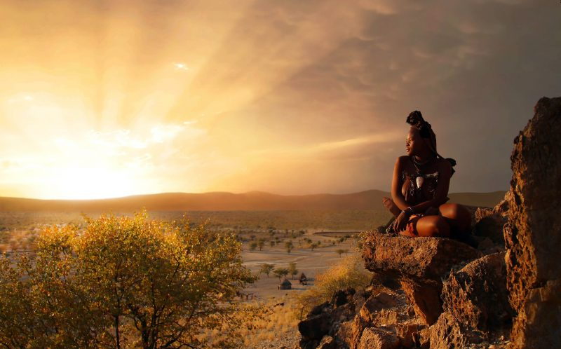 PIC BY BJORN PERSSON / CATERS NEWS - (PICTURED: A member of the Himba Tribe against the stunning backdrop.) - These striking images show an elegant African tribeswoman in traditional dress and mud for sunscreen - checking out deals on washing powder. The woman, from the Himba tribe in Opuwo, Namibia, popped into her local grocery store to pick up a few of lifes essentials.Himba tribespeople lead a very traditional lifestyle, and so the photos reveal the very pervasive nature of globalisation. The lady, thought to be in her early twenties, was pictured by Swedish wildlife and documentary photographer Bjorn Persson. SEE CATERS COPY.