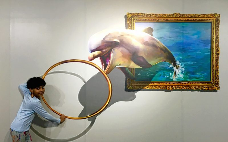 PIC FROM CATERS NEWS - (PICTURED: A child holds a ring that features a painting with a dolphin trying to jump through it.) - Tea with Mona Lisa, a kick from Bruce Lee and a selfie with chimpanzee! This one-of-a-kind museum is giving selfie fans a chance to feature in their favourite works of art. Click Art Museum in southern India is engaging visitors with unique and interactive 3D paintings. Using an art form from the time of the Renaissance Era called Tompe-loeil, which in French means deceive the eye, an Indian artist has revived the paintings for the smart phone generation. From angelic wings to fighting with Alexander the Great, tea with Mona Lisa, getting an apple from Adam and the real bull fight from Spain, there are 24 different 3D art works at the first-of-its-kind trick art museum. With its unique concept, the museum has already received over 75,000 visitors in just six months. SEE CATERS COPY.