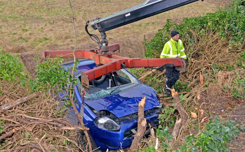 PIC FROM EXPRESS AND STAR/CATERS NEWS - (PICTURED: Bekkies car as workers remove it from the ditch.) - Paramedics feared a student who was millimetres from death had been DECAPITATED after a terrifying car crash. Bekkie Payne, from Wombourne, Staffordshire, is still on morphine 18 months on from the horror smash which put her in hospital for seven weeks. Bekkie, 23, was driving round a roundabout when her car clipped the kerb, sending her Fiat Punto crashing through a wooden fence into a ditch where it then set on fire. A fence panel severed her neck after coming through the windscreen and was just millimetres from a vital artery, with paramedics worrying she had been decapitated. The life-changing accident also left the criminology student with a brain injury, a paralysed left arm, a fractured collarbone, a chipped spine and heavy bruising to her face. SEE CATERS COPY.