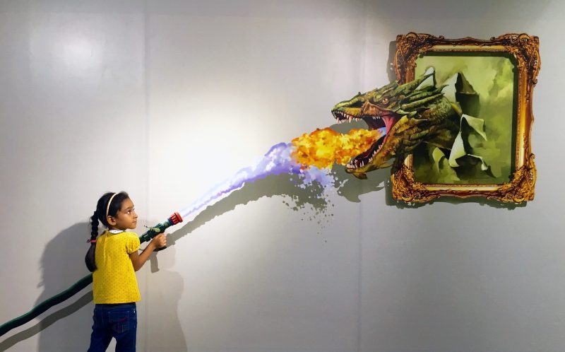 PIC FROM CATERS NEWS - (PICTURED: A little girl poses for a selfie where a dragon appears to be breathing fire towards her.) - Tea with Mona Lisa, a kick from Bruce Lee and a selfie with chimpanzee! This one-of-a-kind museum is giving selfie fans a chance to feature in their favourite works of art. Click Art Museum in southern India is engaging visitors with unique and interactive 3D paintings. Using an art form from the time of the Renaissance Era called Tompe-loeil, which in French means deceive the eye, an Indian artist has revived the paintings for the smart phone generation. From angelic wings to fighting with Alexander the Great, tea with Mona Lisa, getting an apple from Adam and the real bull fight from Spain, there are 24 different 3D art works at the first-of-its-kind trick art museum. With its unique concept, the museum has already received over 75,000 visitors in just six months. SEE CATERS COPY.