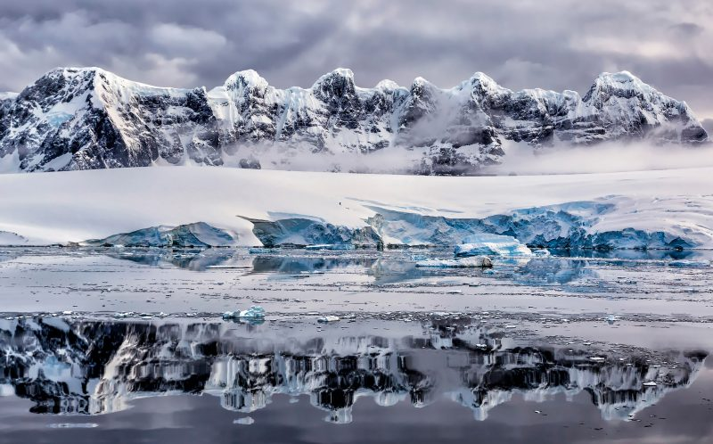 **NOTE TO PICDESKS, PLEASE CREDIT PHOTOGRAPHER NAME/ CATERS NEWS** Pic from Lombardi/Caters News (pic shows mountains and ice reflect of the sea) These BRRR-illiant photographs show the stunning beauty of the Earths frozen Antarctic wilderness. All of these 24 incredible images have been chosen from a short-list of more than 60 as part of the Antarctic Photography Exhibition 2016 at the Tasmanian Museum and Art Gallery. As well as icebergs and frozen landscapes the pictures also encompass the rich wildlife of the South Pole with amazing sightings of characterful penguins, hunting killer whales and basking leopard seals. Bizarrely some of the images provoke a sense of fun with a photograph by Wressel entitled The Meeting which shows two researchers dressed in red meeting two inquisitive emperor penguins. SEE CATERS COPY