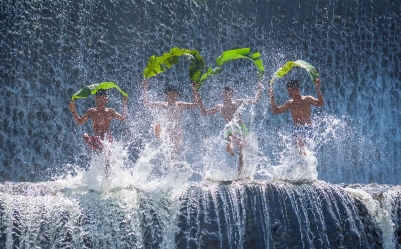 PIC BY AWS ZUHAIR/CATERS NEWS - (PICTURED: A group of four children holding bamboo leaves move in sync in front of a waterfall. ) - Wat-er game these kids are playing, right in front of a giant waterfall! In pictures that look more like a team of synchronised swimmers, four young boys use colourful jugs, umbrellas and banana leaves to create choreographed splashes in the water. The whole scene is played out in front of a towering wall of water in the Unda river on Bali Island, Indonesia. Electrical Engineering PhD student Aws Zuhair Sameen, from Iraq, took the summery snaps on a trip to the country. SEE CATERS COPY.
