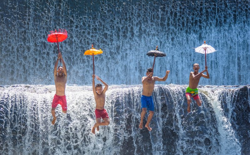 PIC BY AWS ZUHAIR/CATERS NEWS - (PICTURED: A group of four children holding umbrellas jump in sync in front of a waterfall. ) - Wat-er game these kids are playing, right in front of a giant waterfall! In pictures that look more like a team of synchronised swimmers, four young boys use colourful jugs, umbrellas and banana leaves to create choreographed splashes in the water. The whole scene is played out in front of a towering wall of water in the Unda river on Bali Island, Indonesia. Electrical Engineering PhD student Aws Zuhair Sameen, from Iraq, took the summery snaps on a trip to the country. SEE CATERS COPY.