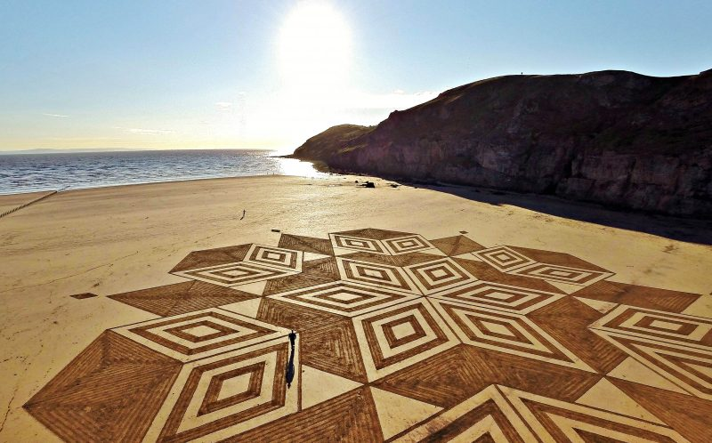 PIC FROM CATERS NEWS (PICTURED: A view of amazing sand art, which consists of geometrical shapes created by talented artist, Julian Richardson at Brean Down in Somerset. ) - These incredible photos show the A-MAZE-ING results of an artists race against time and tides to create sand art. Seen from above, the beautiful patterns stretch of vast swathes of the beach, before the waves roll in reclaim the sand canvas as their own. The artworks were created by Wiltshire artist Julian Richardson, using little more than a rake. Since 2013 he has created 45 sand artworks across the south and west of England, and has even worked with the National Trust. Julian normally works at Brean Down in Somerset, as the Bristol channel has one of the worlds largest tidal ranges and the rocky headland offers a 300ft view over the beach.SEE CATERS COPY