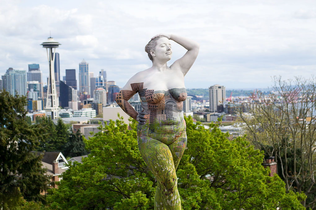 ***MANDATORY BYLINE*** PIC BY TRINA MERRY/CATERS NEWS (PICTURED: A woman blends into the skyline of the city of Seattle, US) - A New York artist has used body paint to perfectly camouflage her subjects into a variety of famous landmarks. Trina Merry, who specialises in bodypainting, line her subjects up and photographed them as they appeared to blend right into the scenery around them. The backdrops to her eye-catching art include the White House, Freedom Tower, Grand Central Station, the Golden Gate Bridge, and even Irelands Giants Causeway. By painting her subjects into a modern background, Trina is putting a modern twist on the oldest art form known to man. SEE CATERS COPY