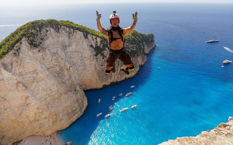 *** MANDATORY BYLINE PIC BY MATT BLANK/ CATERS NEWS *** - (PICTURED: Thibaut Zevaco leaping off the cliff) - This incredible footage of daredevils leaping from a cliff towards clear blue sea will take your breath away. High above a stunning beach with white sands and crystal-clear waters in Zakynthos, Greece, photographer Brian Mosbaugh prepared to take the nail-biting leap. The beautiful Navagio Beach, also known as Shipwreck Beach, sees hundreds of fearless adrenaline junkies tackle its infamous BASE jump. Brian, 31, from Texas, said: The act of human flight is mind-blowing on its own, however flying above Shipwreck Beach was certainly in my top five favourite exits experienced as a BASE jumper. SEE CATERS COPY.