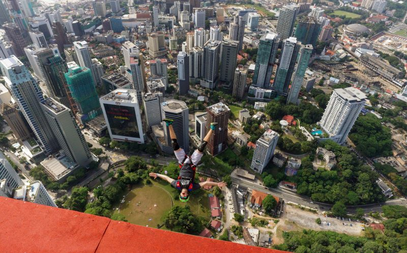 PIC BY MATT BLANK / CATERS NEWS - One of the base jumpers star fishing off the KL Tower.
