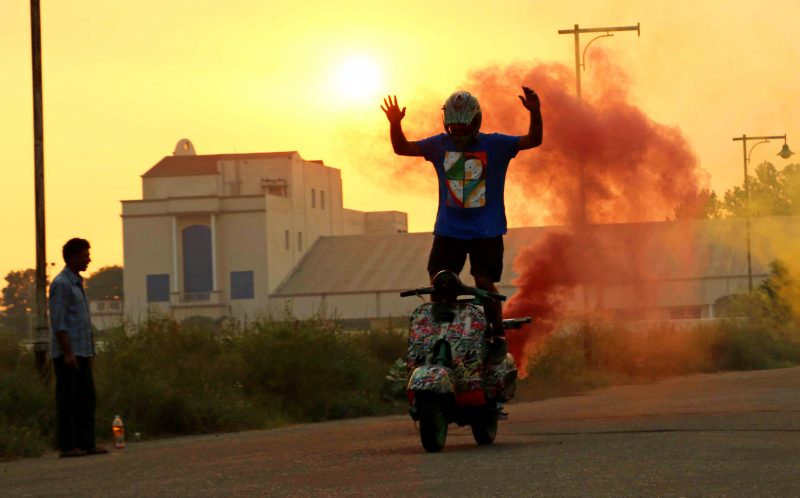 PIC BY AJAY VERMA/ CATERS NEWS - Dinesh Verma performs a stunt on his scooter during sunset.