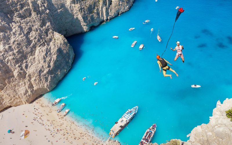 *** MANDATORY PIC BY BRIAN MOSBAUGH/ CATERS NEWS *** - (PICTURED: Two base jumpers jumping over the beautiful Navagio Beach) - This incredible footage of daredevils leaping from a cliff towards clear blue sea will take your breath away. High above a stunning beach with white sands and crystal-clear waters in Zakynthos, Greece, photographer Brian Mosbaugh prepared to take the nail-biting leap. The beautiful Navagio Beach, also known as Shipwreck Beach, sees hundreds of fearless adrenaline junkies tackle its infamous BASE jump. Brian, 31, from Texas, said: The act of human flight is mind-blowing on its own, however flying above Shipwreck Beach was certainly in my top five favourite exits experienced as a BASE jumper. SEE CATERS COPY.