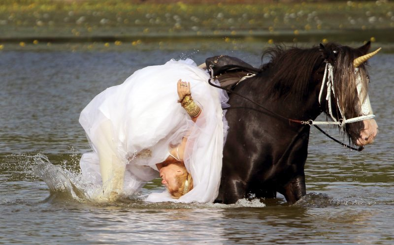 PIC BY TROY ILLOSKI/ CATERS NEWS - This is the hilarious moment a UNICORN ruined a bridal photo shoot. Sue Allegretta, from Oakland, New Jersey, was hoping for a memorable photo shoot with her beloved horse, but ended up falling into the water. Sue - wearing a wedding dress - looked unimpressed as she stood up in the river completely drenched. SEE CATERS COPY