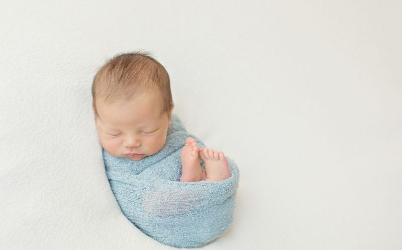 PIC BY ALICIA GOULD/CATERS NEWS - A baby wrapped up in a blue blanket.