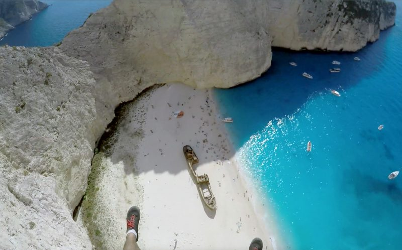 *** MANDATORY PIC BY BRIAN MOSBAUGH/ CATERS NEWS *** - (PICTURED: POV from Brian Mosbaughs head camera ) - This incredible footage of daredevils leaping from a cliff towards clear blue sea will take your breath away. High above a stunning beach with white sands and crystal-clear waters in Zakynthos, Greece, photographer Brian Mosbaugh prepared to take the nail-biting leap. The beautiful Navagio Beach, also known as Shipwreck Beach, sees hundreds of fearless adrenaline junkies tackle its infamous BASE jump. Brian, 31, from Texas, said: The act of human flight is mind-blowing on its own, however flying above Shipwreck Beach was certainly in my top five favourite exits experienced as a BASE jumper. SEE CATERS COPY.