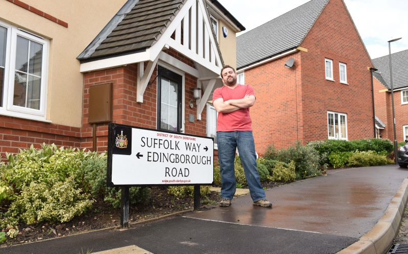 PIC BY MIKEY JONES / CATERS NEWS - (PICTURED Mark Jacobs with the sign ) - A bizarre misspelling of a road sign in a Derbyshire Village has left housing developer red-faced. The miss spelt Edingborough Road sign, that was put up in Church Gresley a week ago by David Wilson Homes, was erected to make it clearer to motorists where Edinburgh Road finished and Suffolk Way began. And it not the first time designers have been left embarrassed by a road sign in the area. In August last year, Derbyshire County Council put up signs near the A38 pointing motorists to Eggington when in fact the correct spelling of the village is Egginton. SEE CATERS COPY