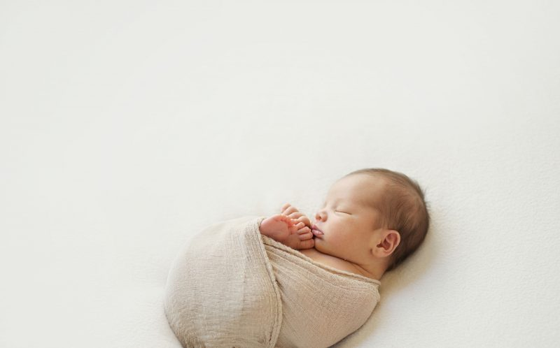 PIC BY ALICIA GOULD/CATERS NEWS - A sleeping baby wrapped up in a beige blanket.