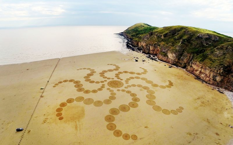 PIC FROM CATERS NEWS (PICTURED: A aerial view of amazing sand art created by talented artist, Julian Richardson at Brean Down in Somerset. ) - These incredible photos show the A-MAZE-ING results of an artists race against time and tides to create sand art. Seen from above, the beautiful patterns stretch of vast swathes of the beach, before the waves roll in reclaim the sand canvas as their own. The artworks were created by Wiltshire artist Julian Richardson, using little more than a rake. Since 2013 he has created 45 sand artworks across the south and west of England, and has even worked with the National Trust. Julian normally works at Brean Down in Somerset, as the Bristol channel has one of the worlds largest tidal ranges and the rocky headland offers a 300ft view over the beach.SEE CATERS COPY