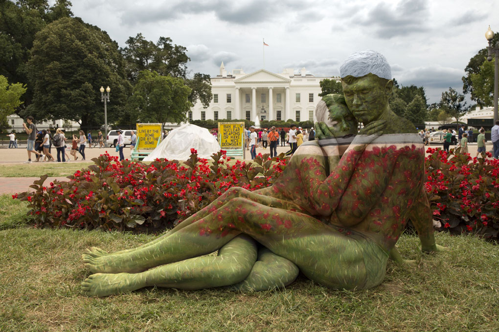***MANDATORY BYLINE*** PIC BY TRINA MERRY/CATERS NEWS (PICTURED: A couple blends into White House and its surroundings in Washington DC, US) - A New York artist has used body paint to perfectly camouflage her subjects into a variety of famous landmarks. Trina Merry, who specialises in bodypainting, line her subjects up and photographed them as they appeared to blend right into the scenery around them. The backdrops to her eye-catching art include the White House, Freedom Tower, Grand Central Station, the Golden Gate Bridge, and even Irelands Giants Causeway. By painting her subjects into a modern background, Trina is putting a modern twist on the oldest art form known to man.SEE CATERS COPY