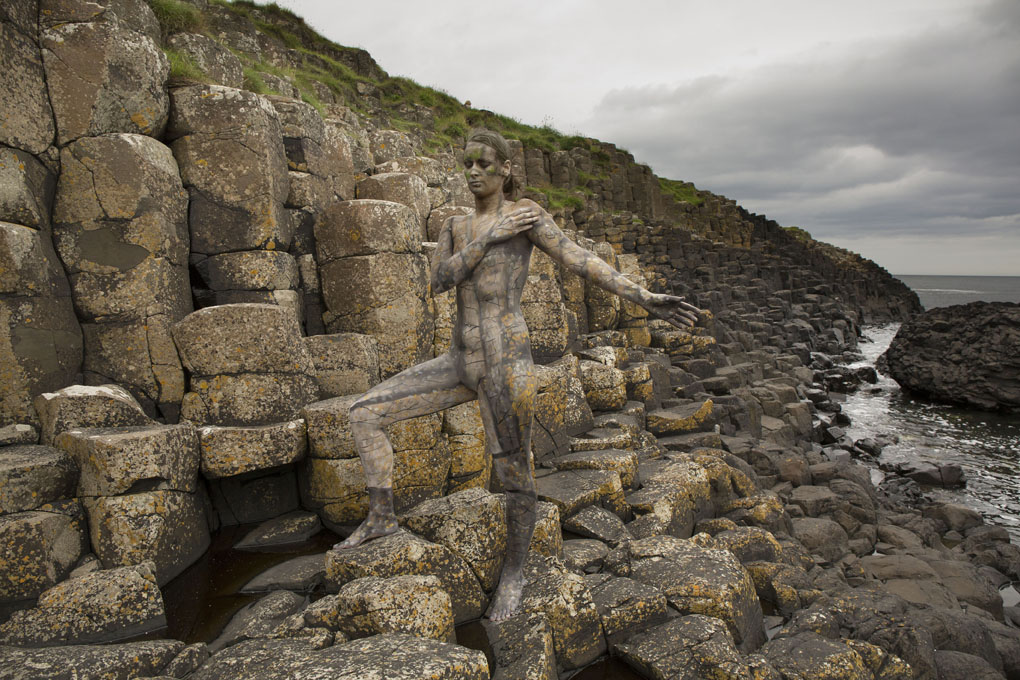 ***MANDATORY BYLINE*** PIC BY TRINA MERRY/CATERS NEWS (PICTURED: A woman becomes one with nature and history at UNESCO World Heritage site Giants Causeway in Buhmills, UK) - A New York artist has used body paint to perfectly camouflage her subjects into a variety of famous landmarks. Trina Merry, who specialises in bodypainting, line her subjects up and photographed them as they appeared to blend right into the scenery around them. The backdrops to her eye-catching art include the White House, Freedom Tower, Grand Central Station, the Golden Gate Bridge, and even Irelands Giants Causeway. By painting her subjects into a modern background, Trina is putting a modern twist on the oldest art form known to man. SEE CATERS COPY