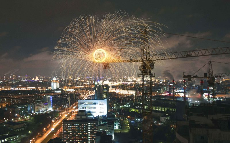 PIC BY DENIS KRASNOV/ CATERS NEWS - (PICTURED: The firework circle being set off ontop of the crane, Moscow) - Friends in Moscow, Russia put on a sparkling display high above the capital citys skyscrapers and captured it beautifully. Russian, Denis Krasnov, 20 from Moscow took the stunning photos of his friends dangerous stunt last month 150 metres up in the night sky. Denis said: We decided to make unusual performance on the top of skyscraper crane. We were preparing it for a month as we were waiting for good weather. Doing this performance, we would like to make the people on the ground a little bit happier. SEE CATERS COPY.