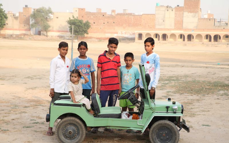 PIC FROM CATERS NEWS - (PICTURED: Children of punjub with Bawar Singhs tiny jeep.) - A 60-year-old pensioner who never went to school has built a miniature jeep which could help the physically challenged. Bawar Singh, who lives in the north Indian state of Punjab, built the innovative vehicle in the backyard of his house and spent the last two years perfecting the design. Singh, who starting working in a car repair shop when he was 18, says he got the idea to built a high performance miniature car in 1975 after a physically challenged person asked him to build an extra set of wheels for his scooter. SEE CATERS COPY.
