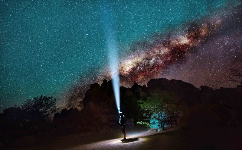 PIC BY PIETRO OLIVETTA/ CATERS NEWS - (PICTURED: Pietro Olivetta shining his torch up to the milky way sky) - Starry, starry night! These explorers set up camp under stars so bright you can read a BOOK in the dead of night. Photographer Pietro Olivetta, from Italy, came across the stunning camping spot whilst exploring with pals in Namibia. The make-shift camp was lit up by thousands of bright stars shining down from the Milky Way, giving the group a striking view of the twinkling sky. The glowing stars shone so brightly that the group, who stayed at the camp for four weeks, could even settle down to read a book after the sun went down. SEE CATERS COPY.