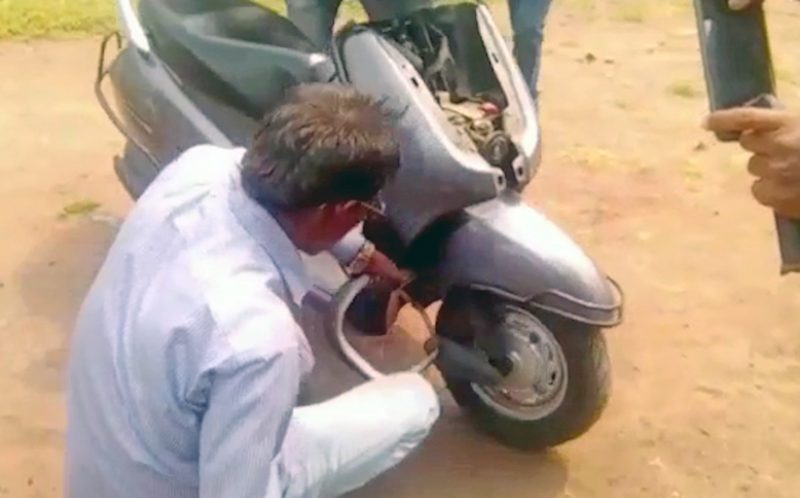 PIC FROM CATERS NEWS - (PICTURED: A rescuer tries to pull a snake free from the inside of a scooter.) - A shocking video shows a deadly cobra stuck in the wheel of a scooter, forcing the driver to jump off in panic. The 8-feet long cobra had apparently made its way into the scooter through the opening under the wheels and slithered its way into the front. The snake sneaked out through the handlebars of the scooter, shocking the rider who was casually navigating his way through a street in Sangli town of India. Shell shocked, the driver abandoned his scooter and called animal rescuers. SEE CATERS COPY.