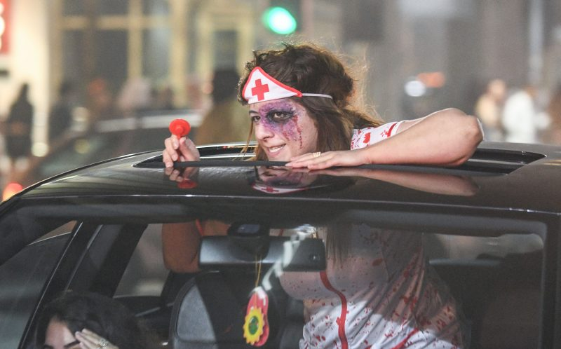 PIC BY MICHAEL SCOTT/CATERS NEWS - (PICTURED: A zombie styled nurse sticks her head out of a sunroof as the driver ducks out of the line of sight from the camera as she continues to drive down Broad Street in Birmingham during the night of Halloween.)It was nightmare on Broad Street last night as thousands of revellers hit the streets for Halloween. Party-goers in Birmingham, West Mids, could be seen collapsed on the floor as paramedics tended to them while another appeared to urinate against a wall. Another guy, dressed in camouflage, was violently sick on the street and a girl was also crouched over vomiting as her friend comforted her. Students went all out with their fancy dress as part of the Nightmare on Broad Street event, which saw over 4,500 people hit the citys infamous strip.