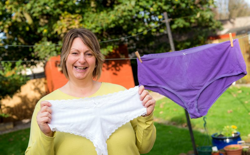 PIC BY FRASER BAND / CATERS NEWS - (PICTURED: Ruth Webster, 46, from Fife hold the pants she wears now vs the super size pants on the washing line.) - A super slimmer is flaunting her weight loss by hanging her shrinking knickers on the washing line after decades of folding them in half. Ruth Webster, 46, from Fife, used to fold her gigantic, size 32, pants in half before putting them out on the line in a bid to deceive her neighbours. For years Ruth battled with her weight until she was finally diagnosed with a binge eating disorder last year which she used as a catalyst to start shedding the pounds for good. After giving up takeaways and sugary snacks, Ruth has dropped seven stone in just ten months - taking her from 26 to 19 stone and shrinking her hips by 20 inches. Ruth started Joe Wicks 90 Day SSS plan, and despite wanting to lose more weight she claims that her undies are proof that the plan works. SEE CATERS COPY.