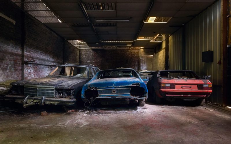 PIC BY ROMAN ROBROEK /CATERS NEWS - (PICTURED: An old storage unit filled with abandoned cars.) - Mother Nature has turned into a scrapyard - as dust, rust and vines clamp and reclaim various abandoned cars. Photographs show a collection of once-grand Rolls Royces, Ferraris, Ford Mustangs and others left to rot all over Europe. Roman, an ICT worker and amateur photographer from the Netherlands, tracked down and photographed the abandoned automobiles. SEE CATERS COPY.