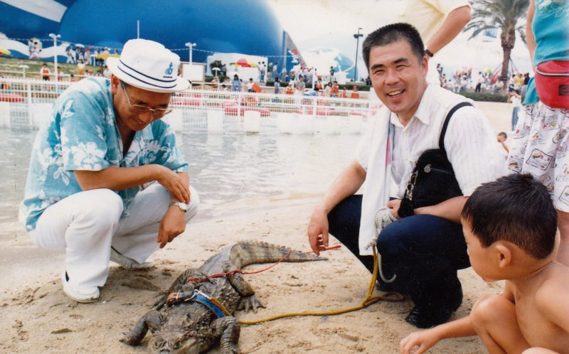 **NO SALES / USE IN JAPAN ** PIC BY 28 LAB / CATERS NEWS - (PICTURED: Nobumitsu Murabayashi, now 65 from Kure City,Hiroshima, Japan pictured with his pet caiman when he was younger.) - Most people settle for cats or dogs as their pet of choice. But one Japanese man has taken things a step further - adopting a giant 6ft 8in caiman. Nobumitsu Murabayashi, 65, can regularly be seen strolling down the road with his unlikely pet - much to the bemusement of passers by. And despite weighing an eye-watering 100lbs, the gentle giant lives inside Mr Murabayashis home in Kure City,Hiroshima, Japan. The pair have been living together for 34 years. SEE CATERS COPY.