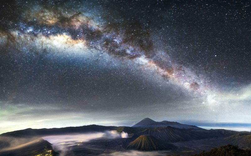 PIC BY GREY CHOW/CATERS NEWS - (PICTURED: The Milky Way over Mount Bromo in Indonesia.) - Thousands of glittering stars lighting up beautiful Indonesian and Malaysian nightscapes will take your breath away. The stunning scenery is bathed in the mystical glow of starlight, and the bright lights of the bustling city below looks like it could be bubbling lava flowing from nearby volcanoes. The incredible pictures were taken by photographer Grey Chow, 30, at Indonesias Mount Bromo and Malaysia. SEE CATERS COPY.