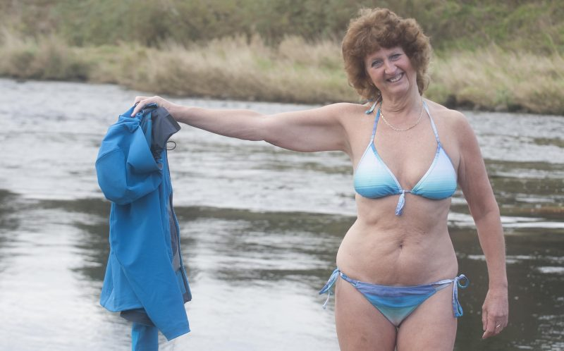PIC BY BEN FURST/MERCURY PRESS (PICTURED: ANN WHEELER, 59 POSES IN HER BIKINI BY A RIVER ) A mum was inspired by a near-death experience to get body confident and go on 20-mile hikes in just a BIKINI and boots to help combat the crippling pain caused by a rare spinal condition - but jealous walkers have told their husbands to KEEP AWAY.Ann Wheeler, from Clayton-le-Woods, Lancashire, suffers from Cauda Equina syndrome - a condition that can cause paralysis.The 59-year-old mum of two claims that the post-op experience motivated her to take up walking and wild swimming as natural pain management as she believes it is as strong as traditional painkillers.However Anns confidence crusade has been met with some criticism online with some women even ordering their walker husbands to steer clear of her.All the exercise has also helped her ditch the pounds going from a size 16 to a slinky size 12 and shes even been approached to pose for a naked charity calendar. SEE MERCURY COPY