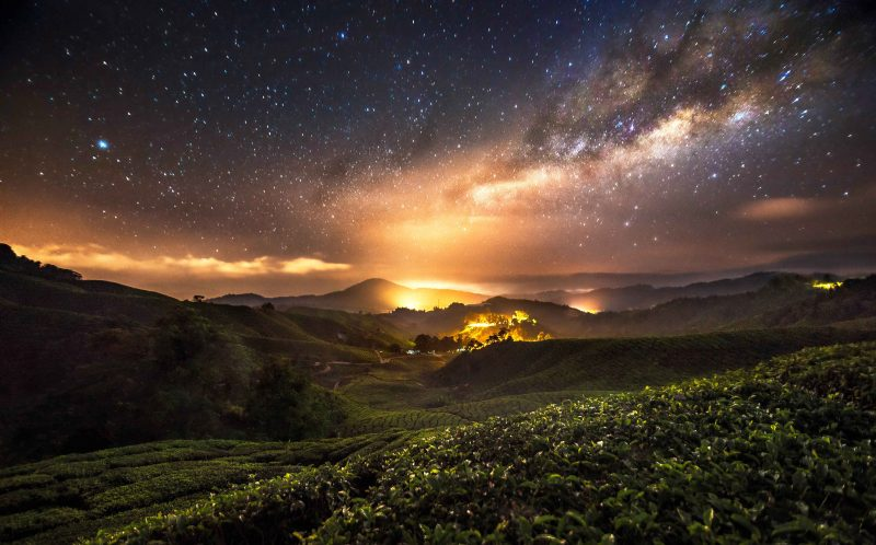 PIC BY GREY CHOW/CATERS NEWS - (PICTURED: A view of the Milky Way in Malaysia.) - Thousands of glittering stars lighting up beautiful Indonesian and Malaysian nightscapes will take your breath away. The stunning scenery is bathed in the mystical glow of starlight, and the bright lights of the bustling city below looks like it could be bubbling lava flowing from nearby volcanoes. The incredible pictures were taken by photographer Grey Chow, 30, at Indonesias Mount Bromo and Malaysia. SEE CATERS COPY.