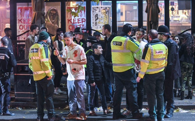 PIC BY MICHAEL SCOTT/CATERS NEWS - (PICTURED: Police and paramedics diffuse ealrier tensions as nightclubs start to turn out at the end of the Halloween night on Birminghams Broad Street.)It was nightmare on Broad Street last night as thousands of revellers hit the streets for Halloween. Party-goers in Birmingham, West Mids, could be seen collapsed on the floor as paramedics tended to them while another appeared to urinate against a wall. Another guy, dressed in camouflage, was violently sick on the street and a girl was also crouched over vomiting as her friend comforted her. Students went all out with their fancy dress as part of the Nightmare on Broad Street event, which saw over 4,500 people hit the citys infamous strip.