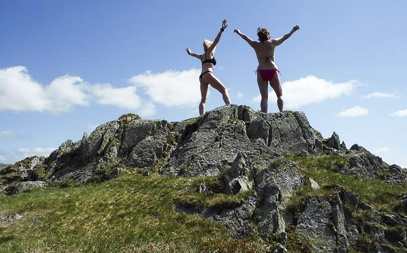 PIC FROM MERCURY PRESS (PICTURED: ANN WHEELER, 59 POSES TOPLESS WITH A FRIEND IN THE LAKE DISTRICT, WHERE SHE LIKES TO SWIM ) A mum was inspired by a near-death experience to get body confident and go on 20-mile hikes in just a BIKINI and boots to help combat the crippling pain caused by a rare spinal condition - but jealous walkers have told their husbands to KEEP AWAY.Ann Wheeler, from Clayton-le-Woods, Lancashire, suffers from Cauda Equina syndrome - a condition that can cause paralysis.The 59-year-old mum of two claims that the post-op experience motivated her to take up walking and wild swimming as natural pain management as she believes it is as strong as traditional painkillers.However Anns confidence crusade has been met with some criticism online with some women even ordering their walker husbands to steer clear of her.All the exercise has also helped her ditch the pounds going from a size 16 to a slinky size 12 and shes even been approached to pose for a naked charity calendar. SEE MERCURY COPY