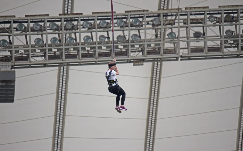 PIC BY CATERS NEWS - (PICTURED: A daredevil jumps from The Big Rush, Africa.) - Adrenaline junkies can now test their head for heights by leaping from the top of a football stadium on the worlds tallest swing. Set at the highest point of the Moses Mabhida Stadium in South Africa, The Big Rush invites those brave enough to leap from the top and swing across the world famous pitch. At 88 metres high, thrillseekers can quite literally swing from the rafters as they leap from the top of the stadium, home of the 2010 FIFA World Cup. Named the tallest swing by The Guinness World Records, The Big Rush in Durban, South Africa, sees brave participants climb 352 steps to reach the stadiums iconic arch of triumph. - SEE CATERS COPY